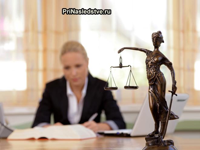 Статуэтка Фемиды, на заднем плане девушка-юрист