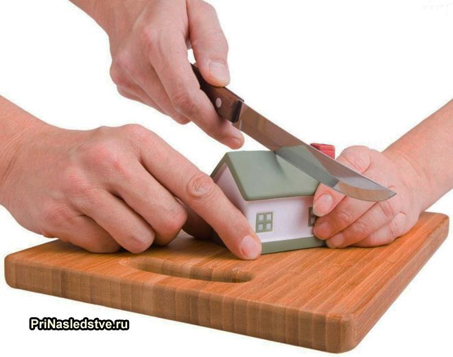 Игрушечный домик разрезают пополам на разделочной доске