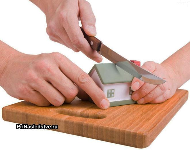 Игрушечный домик разрезают на разделочной доске