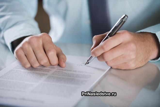 Мужчина в деловом костюме подписывает документы