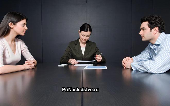 Мужчина и женщина сидят друг напротив друга на приеме у нотариуса