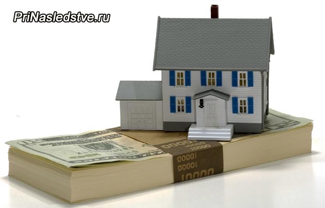Игрушечный домик стоит на пачке денег