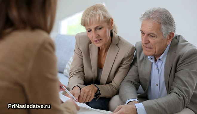 Семейная пара в возрасте читает документы у юриста