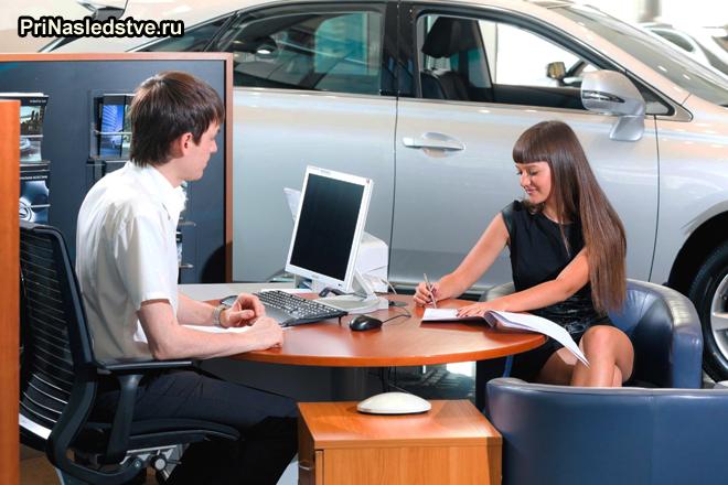 Девушка оформляет документы в автосалоне