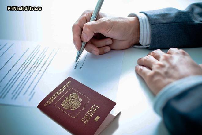 Мужчина подписывает договор, рядом лежит паспорт