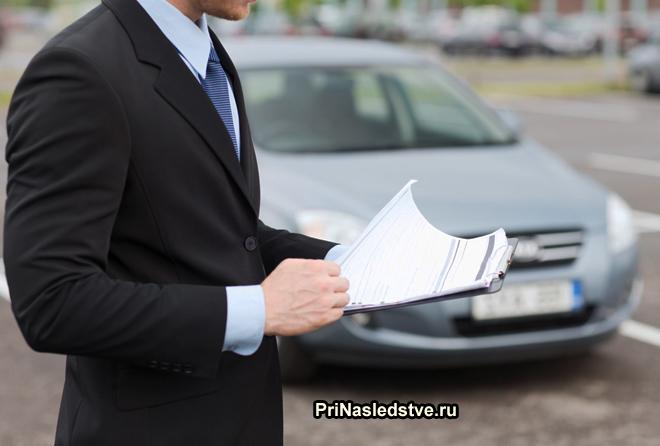 Мужчина в деловом костюме смотрит документы на машину