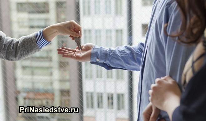 Девушка передает ключи от квартиры молодой паре
