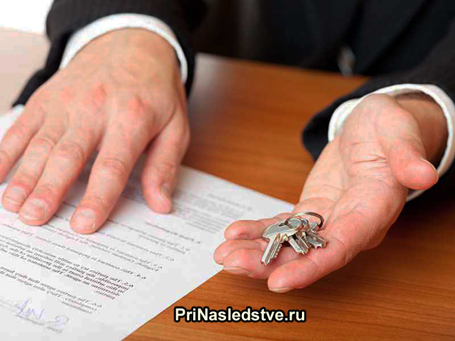 Бизнесмен держит ключи от квартиры и рядом лежит договор