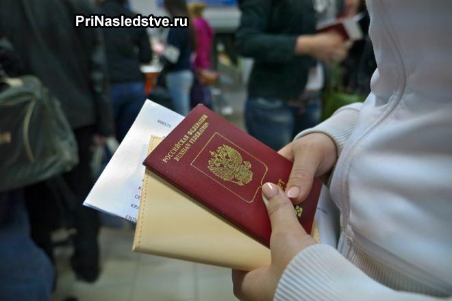 Девушка стоит с документами в очереди