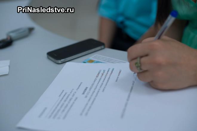 Девушка заполняет заявление на бумаге
