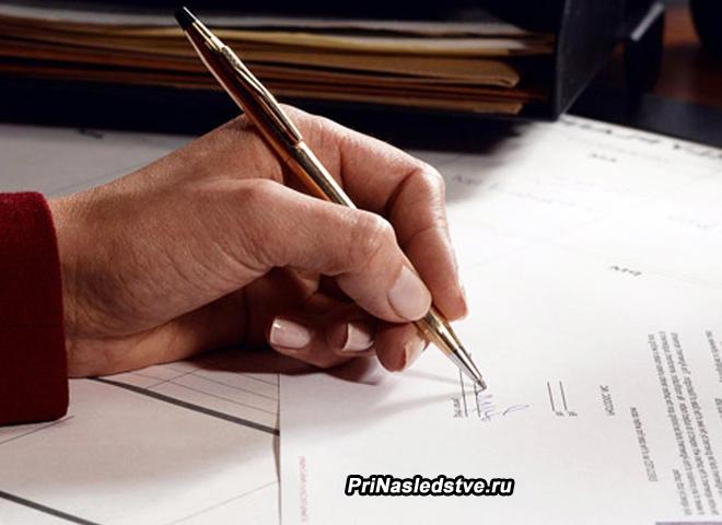 Мужчина ставит свою подпись на документах