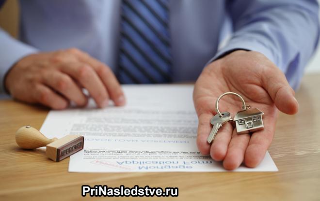 Мужчина держит в руке ключи, на столе лежат документы