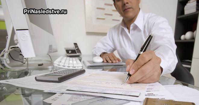 Мужчина сидит за рабочим местом и подписывает документы
