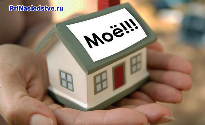 """Девушка держит в руках игрушечный домик с надписью """"мое"""""""