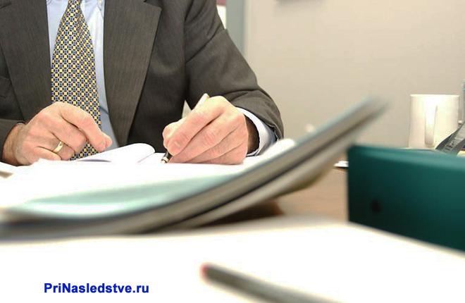 Бизнесмен расписывается в документах