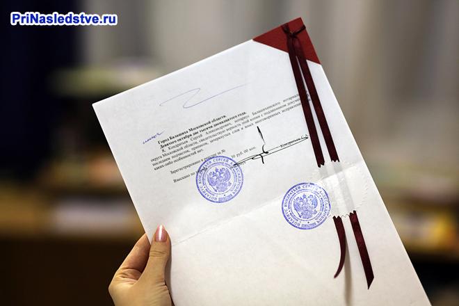 Девушка держит в руке документ с печатями