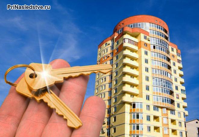Мужчина держит в руке ключи от квартиры в новостройке