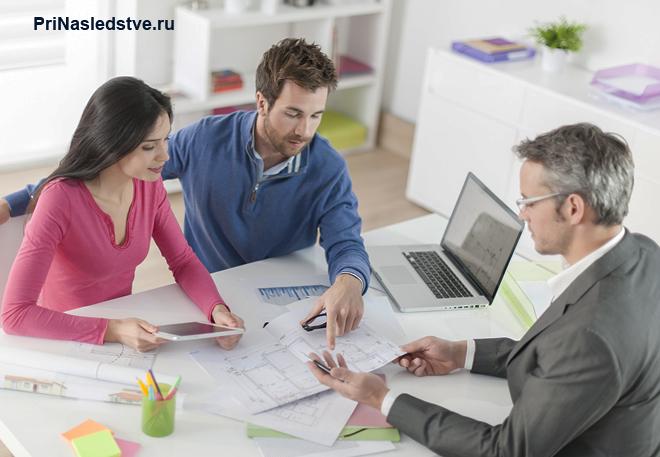Молодая семья и мужчина общаются в офисе