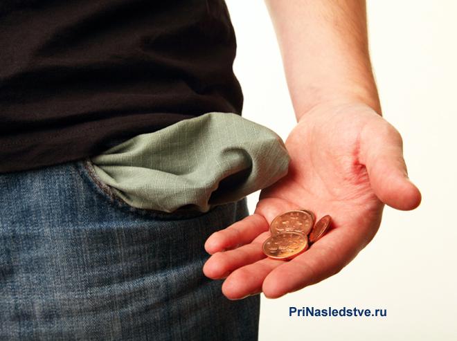 Молодой человек достал монеты из кармана джинс
