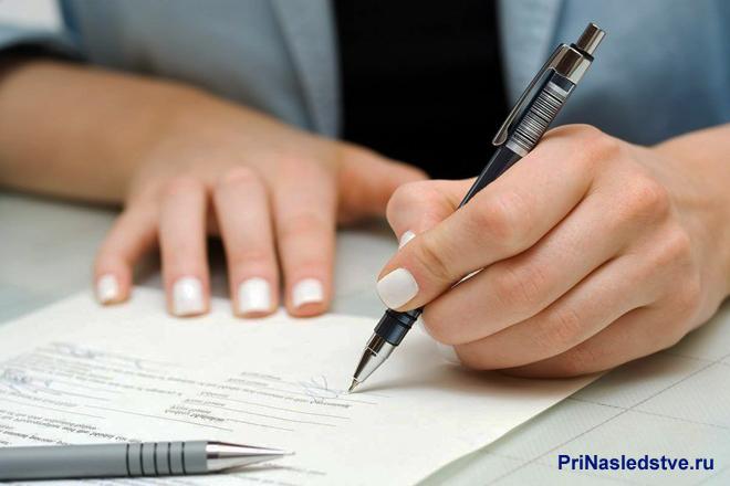 Девушка подписывает документы