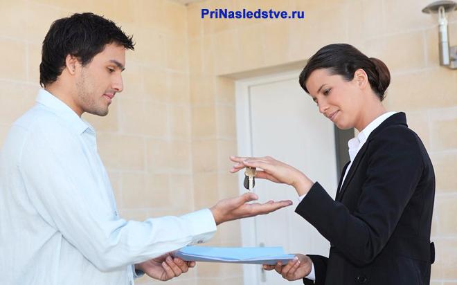 Мужчина передает женщине ключи и документы