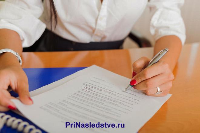 Девушка в белой рубашке подписывает документы