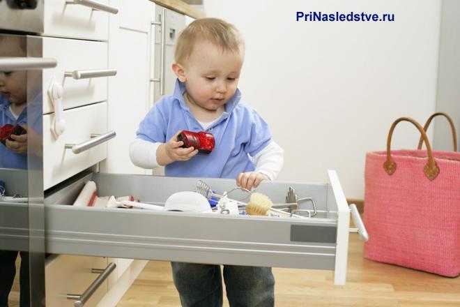 Мальчик достает игрушки из комода