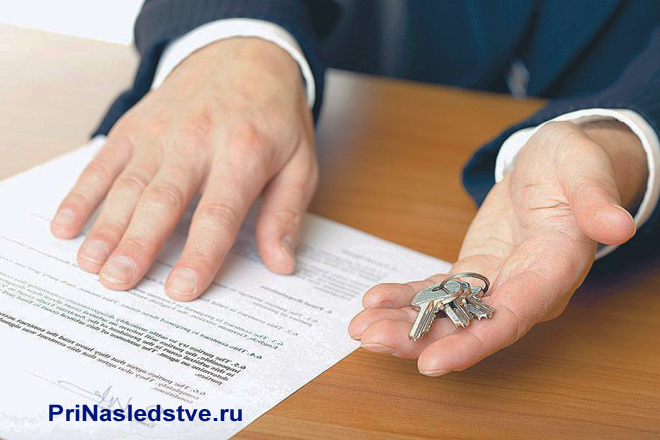 Бизнесмен держит в руке ключи
