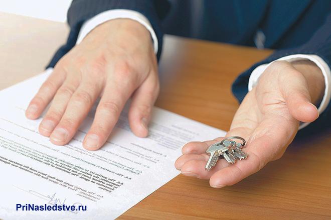Бизнесмен держит в руке ключи, рядом лежит договор
