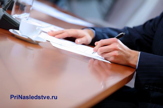 Бизнесмен сидит за столом и подписывает документы