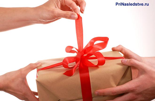 Люди распаковывают подарок в упаковке