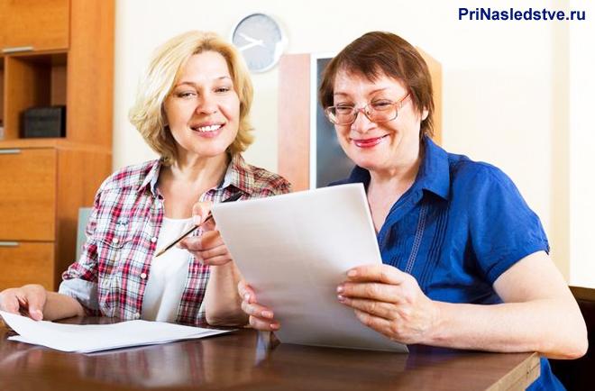 Девушка и женщина в возрасте сидят за столом и читают документы