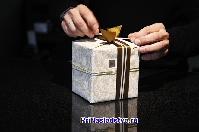Мужчина распаковывает подарок
