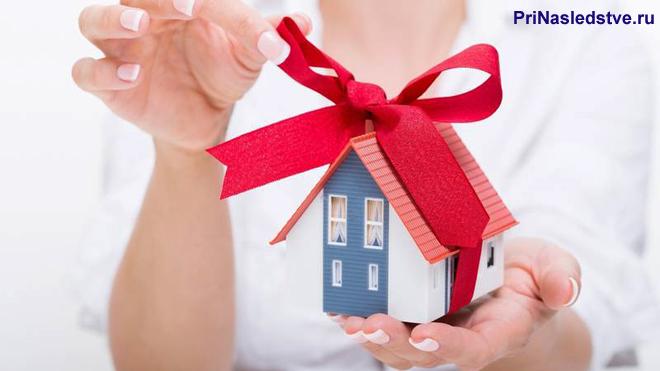 Девушка развязывает красный бантик на домике
