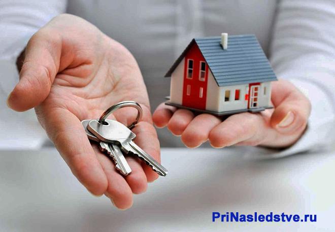Мужчина держит в руке макет домика и ключи