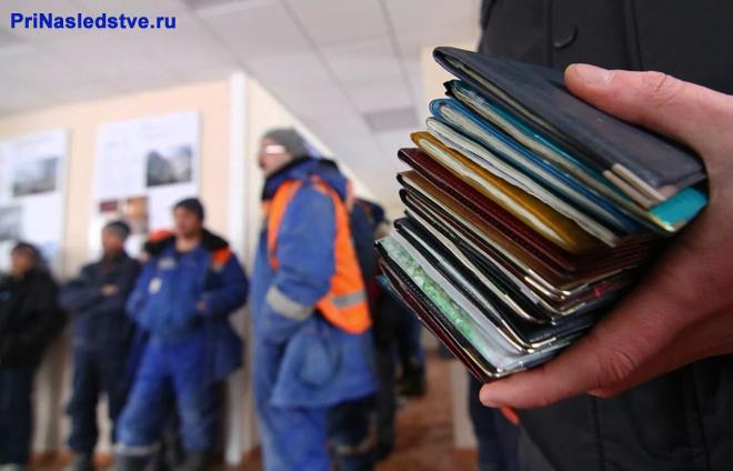 Человек держит в руке паспорта, на заднем фоне стоят рабочие