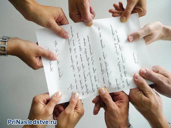 Люди делят между собой лист бумаги
