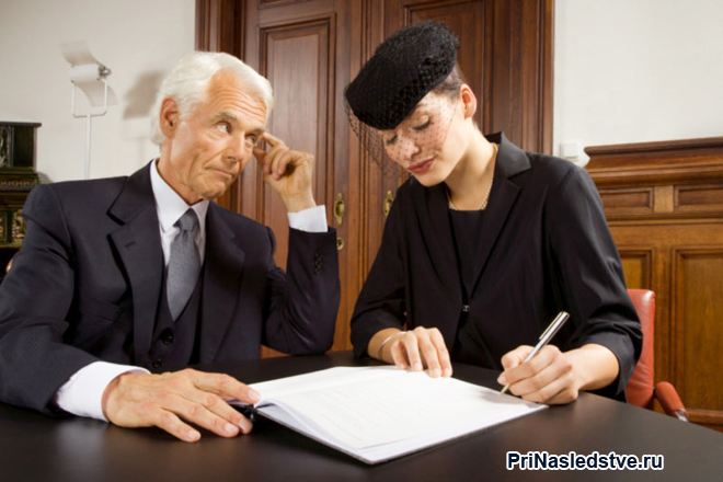 Женщина в черном и юрист изучают документы