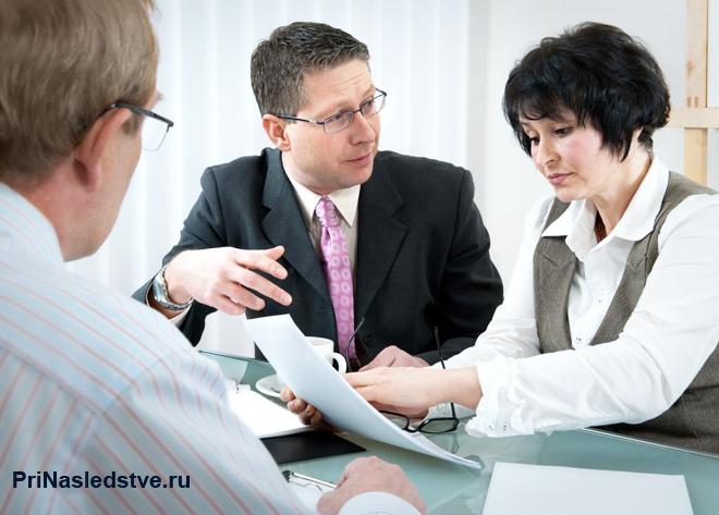Двое мужчин и женщина изучают документы