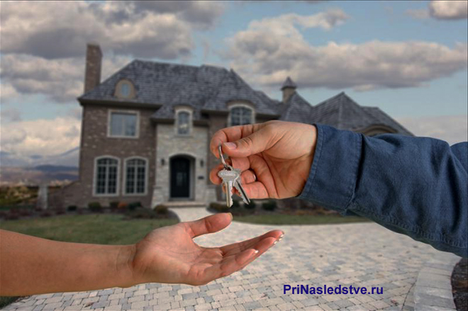 Мужчина передает ключи на фоне частного дома