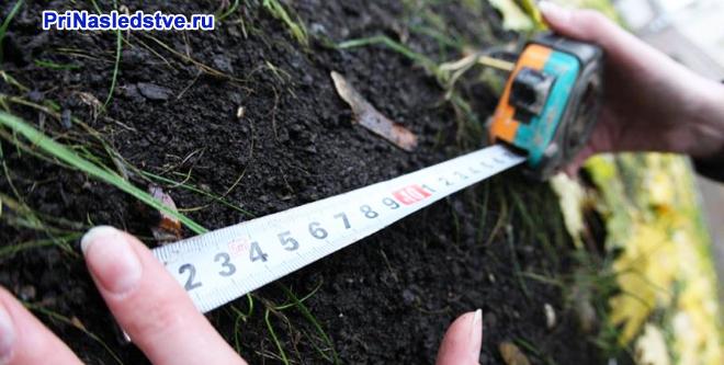 Девушка измеряет участок земли сантиметром