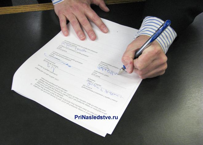 Мужчина в полосатой рубашке пишет ручкой на листе за столом