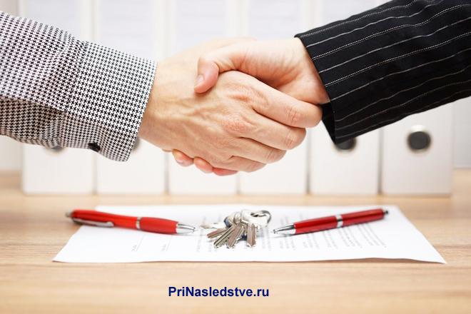 Мужчины в деловых костюмах жмут друг другу руку