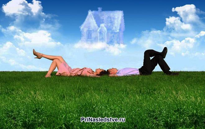 Семейная пара лежит на травке и мечтает о своем доме