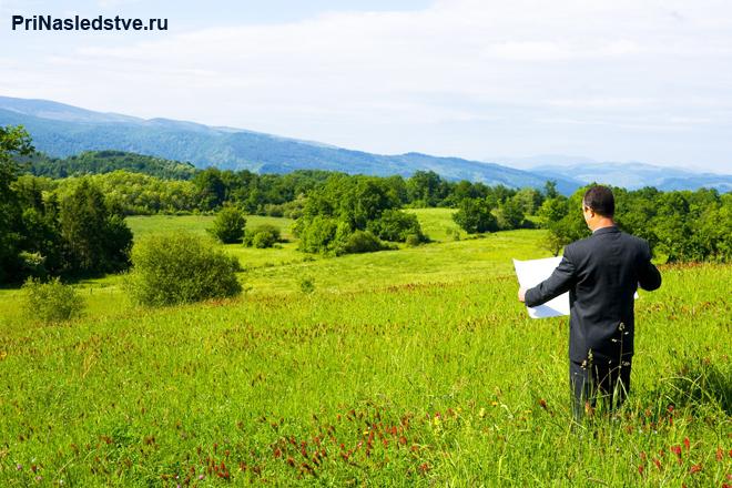 Бизнесмен стоит с планом на поле