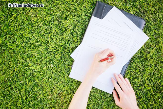 Девушка оформляет документы, лежа на зеленой травке