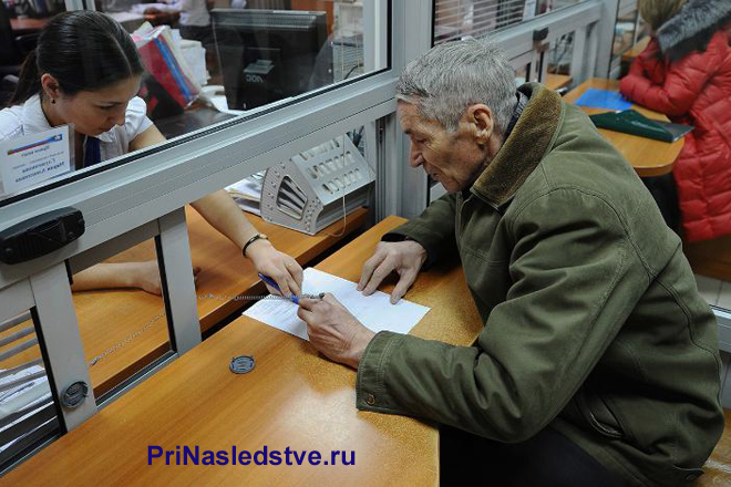 Пенсионер сидит около окна приема граждан