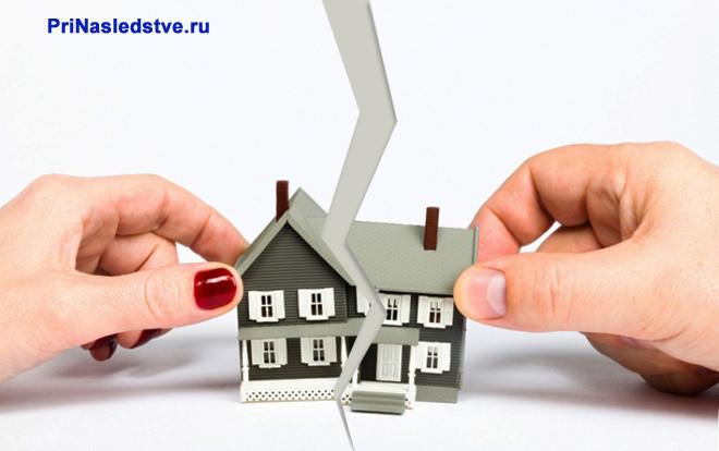 Девушка рвет лист бумаги, на котором изображен дом