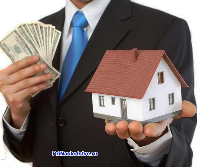 Бизнесмен держит в руках игрушечный домик и деньги