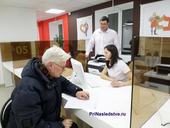 Мужчина сидит рядом с окном приема, сотрудники в белых рубашках на заднем фоне